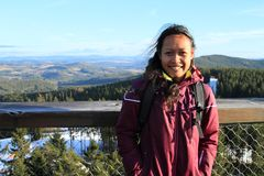 Tourist on The trail trees Lipno Lookout. Smiling Papuan tourist girl - young woman in purple jacket standing on The trail trees Lipno Lookout with Sumava Royalty Free Stock Photos