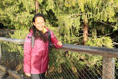 Tourist on The trail trees Lipno Lookout. Smiling Papuan tourist girl - young woman in purple jacket on The trail trees Lipno Lookout in Czech Republic Royalty Free Stock Images