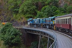 A tourist train of Kuranda Scenic Railway moving through the forest area on top of a dramatic bridge. The train offers the transportation and amazing view of stock images
