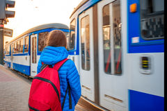 Tourist on the tram station. Young female tourist in blue jacket with backpack on the station with blue tram on backround. Motion effect Royalty Free Stock Photo