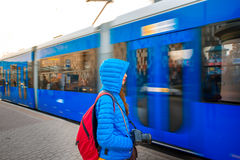 Tourist on the tram station. Young female tourist in blue jacket with backpack on the station with blue tram on backround. Motion effect Stock Images