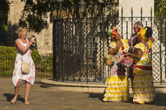 Tourist trap Havana. Tourists photographing Cuban women in colorful traditional clthes at Plaza de Armas in Old Havana (Spanish: Habana Vieja), Cuba Stock Photo