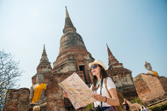 Tourist on travel sightseeing holding map. Ayutthaya tourist woman on asia travel sightseeing holding map by Wat Yai Chai Mongkhon temple. Tourism people concept Stock Photography