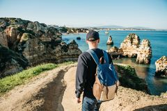 Tourist or traveler with a backpack on the Atlantic coast. A tourist or traveler with a backpack admires the beautiful view of the Atlantic Ocean and the coast Royalty Free Stock Photo