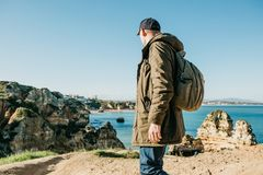 Tourist or traveler with a backpack on the Atlantic coast. A tourist or traveler with a backpack admires the beautiful view of the Atlantic Ocean and the coast Royalty Free Stock Images