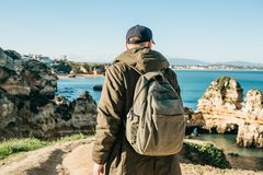 Tourist or traveler with a backpack on the Atlantic coast. A tourist or traveler with a backpack admires the beautiful view of the Atlantic Ocean and the coast Stock Photo