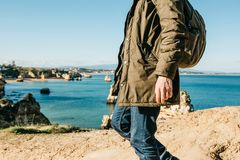 Tourist or traveler with a backpack on the Atlantic coast. A tourist or traveler with a backpack walks along the coast of the Atlantic Ocean and admires the Stock Image