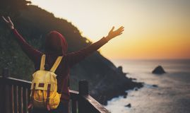 Tourist traveler with backpack standing with raised hands, hiker looking on sunset to valley in trip, hipster young girl enjoying. Peak of mountain background stock photos