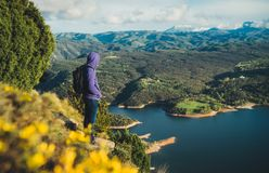 Tourist traveler with backpack on top mountain and enjoys river, hiker relax looking on blue sky clouds, background nature panoram royalty free stock image