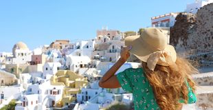 Tourist traveler girl in Oia, Santorini island in Greece. Europe travel summer vacation woman holding her hat and enjoying. Panoramic view stock images