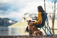 Free Tourist Traveler Girl Rest Together Dog On Background Mountain, Woman Drink Tea Hugging Puppy Pet On Lake Shore Nature Trip Royalty Free Stock Image - 170755886