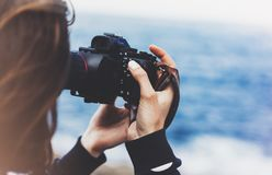 Tourist traveler photographer girl taking pictures of seascape on modern photo camera on background blue ocean view mockup sun royalty free stock image