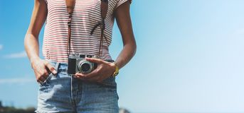 Tourist traveler photographer making pictures holding photo camera on background ocean sea scape, hipster girl looking on nature h. Orizon, relax holiday, blank Royalty Free Stock Photo