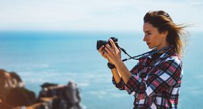 Tourist traveler photographer making pictures sea scape on photo camera on background ocean, hipster girl looking on nature horizo. N, relax holiday, blank space Stock Images