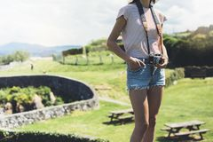 Tourist traveler photographer making pictures sea scape on vintage photo camera on background ocean, hipster girl enjoying green. Peak mountain and nature royalty free stock image