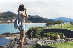 Tourist traveler photographer making pictures sea scape on vintage photo camera on background ocean, hipster girl enjoying green royalty free stock photos