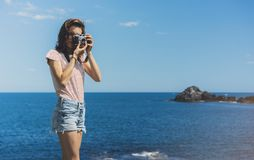 Tourist traveler photographer making pictures sea scape on vintage photo camera on background yacht and boat piar, hipster girl stock photography