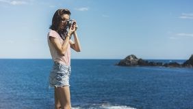 Tourist traveler photographer making pictures sea scape on vintage photo camera on background yacht and boat piar, hipster girl stock image
