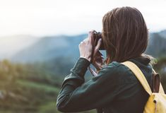 Tourist traveler photographer taking pictures of amazing landscape on vintage photo camera on background valley view mockup sun royalty free stock photography