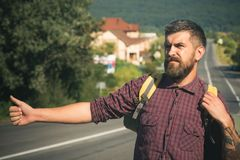 Tourist traveler travel auto stop. Hipster hiker show thumbs up hand gesture on sunny day. Adventure, discovery, wanderlust. Man with backpack hitchhiking on stock photo