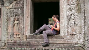 Tourist traveling preah khan temple read book, angkor, cambodia stock video footage