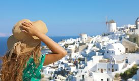 Tourist traveling in Santorini, Oia island in Greece, Europe travel summer vacation woman relaxing at view windmills. Holiday girl. In hat and green flowered stock images