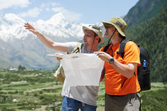 Tourist travellers with map in mountains Stock Photos