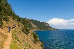 Tourist trek at Baikal lake. Tourists walking on the Baikal lake shore Royalty Free Stock Photography