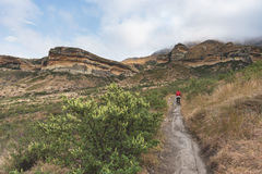 Tourist trekking on marked trail in the Golden Gate Highlands National Park, South Africa. Scenic table mountains, canyons and cli Royalty Free Stock Images