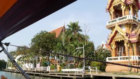 Tourist trip on Asian canal. View of calm channel and residential houses from decorated traditional Thai boat during stock video footage