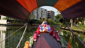Tourist trip on Asian canal. View of calm channel and residential houses from decorated traditional Thai boat during stock footage