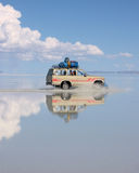Tourist Trip, Bolivia. SALAR DE UYUNI, BOLIVIA, 5 JANUARY 2006: Tourists travelling in an old Jeep across the flooded salt plains of Bolivia. It is the worlds Royalty Free Stock Photo