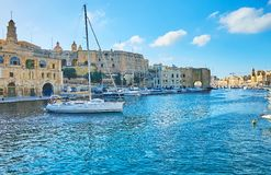 The tourist trip on sailing yacht, Birgu, Malta. BIRGU, MALTA - JUNE 17, 2018: Scenic sail yacht floats in marina of Vittoriosa with a view on medieval St Royalty Free Stock Image