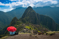 Tourist under red umbrella at Machu Picchu Stock Images