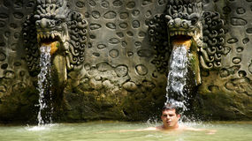 Tourist underneath ornamental Bali water sources Royalty Free Stock Images