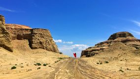 Tourist and Urho Ghost City, Xinjiang China. A lady is walking in Urho Gohost City. Yardang landforms in Xinjiang,China. Located 100 km northeast of Karamay Royalty Free Stock Images