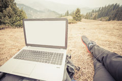 Tourist uses laptop remotely and relax at mountain Stock Photography