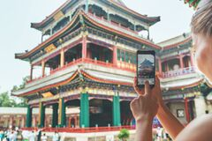 Free Tourist Using Mobile Phone Screen For Picture With Smartphone Of Old Lama Temple In Beijing, China. Asia Tourism Travel Stock Image - 220964401