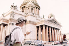 Tourist using navigation app on the mobile phone. Isaakievskiy Sobor in Saint Petersburg on background. Tourist using navigation app on the mobile phone. Travel Royalty Free Stock Photos