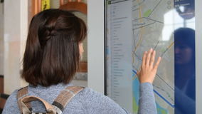 Tourist using searching on touchscreen electronic map. Young woman tourist with backpack using electronic city map on touchscreen to find the place and route stock video