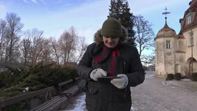 Tourist using tablet near medieval castle in winter stock footage