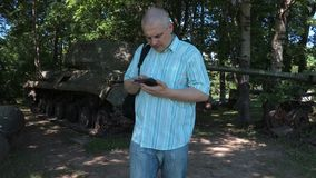 Tourist using tablet at the tank of the second world war stock footage