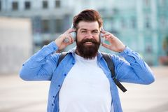 Tourist vacation. Hipster modern tourist urban background. Tourist handsome hipster with backpack headphones. Man with royalty free stock photo