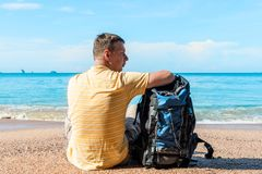 Tourist on vacation at sea, a man with a backpack in a hike. On a halt Royalty Free Stock Photo