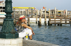 Tourist. In Venice with a summer hat admiring the sea and waiting for a water taxi Royalty Free Stock Image