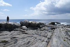 Tourist Viewing Maine's Rocky Coast. Silhouetted figure astride rocky coastline of Maine's shoreline with Atlantic Ocean and clouded blue sky in background Stock Images