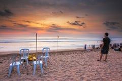 Tourist viewing sunset at Kuta Beach, Bali. Stock Image