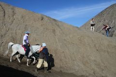 Tourist  and a Villager Riding Horse at Mount Bromo Royalty Free Stock Photo