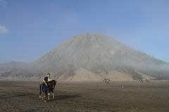 Tourist  and a Villager Riding Horse at Mount Bromo Royalty Free Stock Image