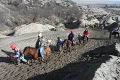 Tourist  and a Villager Riding Horse at Mount Bromo Stock Photo